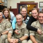 Helping their husbands attach their new senior non-commissioned officers ranks on to their...