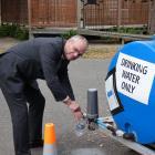 Roxburgh Area School principal Paul McDowall fills a bottle of water from a tank on school...
