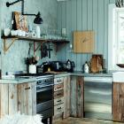 The kitchen in this Norwegian cabin is a harmonious mix of various rustic materials and finishes,...