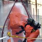Two firefighters in hazmat suits are hosed down in the aftermath of a chemical spill at the PBT...