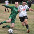 Green Island's Aaron Allan seeks to knock the ball away from Roslyn Wakari's Karma Gyeltshen...