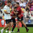 Codie Taylor and Richie Mo'unga celebrate during their dominant win over the Hurricanes in...