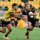 The Chiefs' Damian McKenzie tries to get past Billy Proctor of the Hurricanes. Photo: Getty