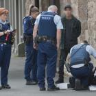 Dunedin police officers search a man's bag in Princes St after an alleged attempt to steal...