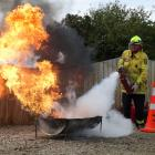 One of the Kakanui Voluntary Rural Fire Force's firefighters demonstrates extinguishing a fire...