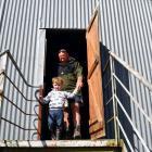 Farmer Cameron Clark, of Owaka, helps his grandson Clay (3) down the back entrance to the auction...