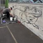 Artist Bruce Mahalski paints a monochrome tuatara mural in Waitati. PHOTO: SUPPLIED