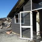 One house on a Wanaka property, pictured in the foreground, was badly damaged while the other, in...