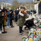 People leave floral tributes outside Buckingham Palace in London following the death of Prince...