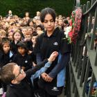 Anderson's Bay School pupils Sidney Austin (5) and Joulia Dibo (10) place a wreath on the school...