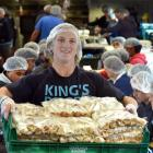 Holding some of the 44,000 individual cheese rolls made at Kings High School yesterday is pupil...