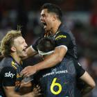 A jubilant Damian McKenzie (left) celebrates with Anton Lienert-Brown (top) and Mitchell Brown...