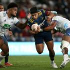 Josh Ioane of the Highlanders is tackled by Akira Ioane of the Blues tonight. Photo: Getty Images