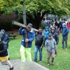 Carrying a cross into St Peter's Anglican Church at the head of a Walk of the Cross procession in...