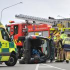 Emergency services attend the scene where a vehicle rolled in Highgate yesterday. PHOTO:...