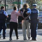 The accused is taken away by police following the incident in at Countdown in central Dunedin...