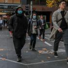 People walk through the CBD in Melbourne, where health authorities are investigating the source...