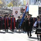 The University of Otago graduation parade moves along George St towards the Dunedin Town Hall...