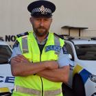 Standing before a pair of police cars in Dunedin, Otago coastal road policing manager Senior...