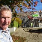 Meadowstone resident David Evans in front of a two-storey unit being built in the Roys Bay Estate...