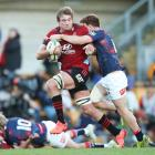 Ethan Blackadder of the Crusaders is brought down during their 52-26 win over the Rebels in...