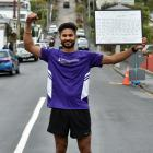 Dairy farmer Harjinder Singh Chander holds a white board recording his success at running up and...