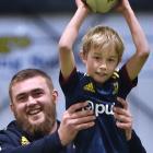 Highlander Jeff Thwaites lifts Levi Stafford (7) of Dunedin during Highlanders coaching kids at...