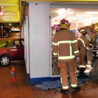 Firefighters access the Night 'n Day in the Octagon yesterday morning after a car drove through...