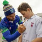 Mairehau Primary School pupil Kalo Willetts gets his school jersey signed by former Warrior Ruben...
