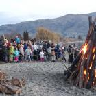 Crowds gather around the bonfires as the temperature started dropping and they waited for the...
