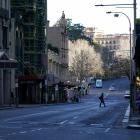 A pedestrian crosses an almost empty street in the centre of Sydney, which is in lockdown until...