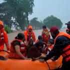 Rescue workers evacuate people from a flooded area in Kolhapur in the western state of...