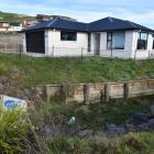 The owners of this Mosgiel home have been told to fix a retaining wall on their property or face...