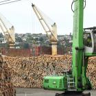 Logs are stacked in the yard at the same time as being loaded on to bulk carrier Blue Everton ...