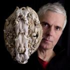 Showing off  a previous work, a bone collage mask, is Dunedin artist and World of WearableArt...