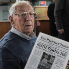Keith Prentice shows the newspaper made by his family about his life to celebrate his 100th...