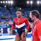USA's Simone Biles is consoled after competing on the vault and withdrawing from the women's all...