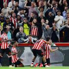 Brentford fans and players celebrate their second goal against Arsenal to kick off their first...
