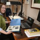 Clutha District Council's community heritage co-ordinator Tiffany Jenks works on her scanning...