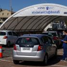 Medical workers speak with members of the public at the Bondi Beach coronavirus testing centre in...
