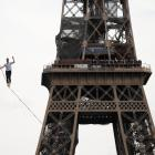 French acrobat Nathan Paulin walks on a slackline between the Eiffel Tower and the Theatre...