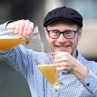 Pouring a fresh glass of upcycled ginger beer, brewed using old bread and damaged fruit, is...