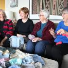 Kathryn Tovgaard, Debbie Woolf, Pat Edward and Barbara Crooks have knitted almost 100 garments...