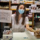 A pharmacist gives a person one of the masks that the Government of Cataluña, Spain has started...
