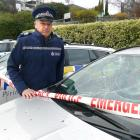 Sergeant Simon Matheson, of Queenstown, with some of the police patrol vehicles damaged in July....