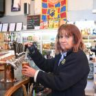Golden Fleece Hotel and Motel co-owner Rose Cayford pours one of the first drinks after the...