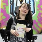 Tayla Sloot (25), of Dunedin, shows her new book My Life with Cerebral Palsy which helps children...