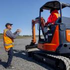 Isaac Construction roading supervisor Paul Coulter teaching someone how to use an excavator at a...
