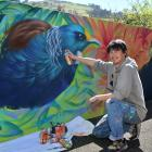 Applying the finer details to his latest mural at Ross Home & Hospital in Dunedin is street...