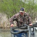 Otago Fish & Game field officer Steve Dixon liberates 500 year-old rainbow trout into Moke...
